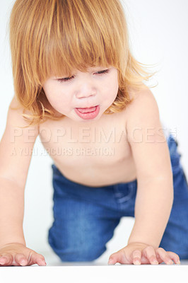Buy stock photo A cute baby looking misrable as she crawls on the floor