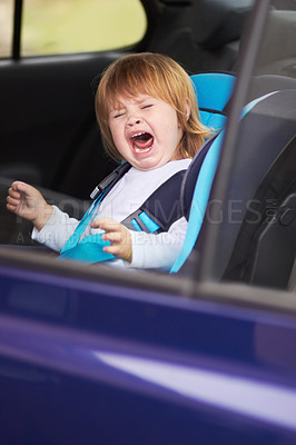 Buy stock photo A crying baby sitting in a carseat in a car