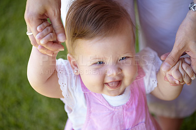 Buy stock photo A cute baby girl  walking in the garden while holding her mother's hands