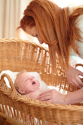 Buy stock photo A baby boy being checked on by his mother while lying in his bassinet
