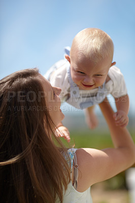 Buy stock photo A cute toddler being held up by his mother in their garden