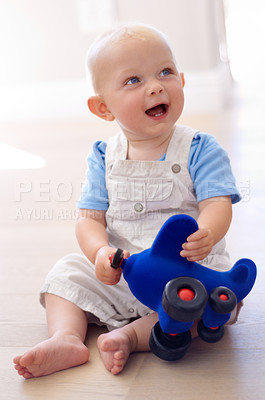 Buy stock photo A cute baby boy sitting on the floor and playing with a toy