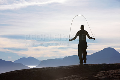 Buy stock photo Rearview of a man skipping on a mountain top