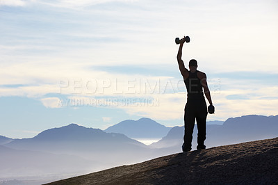 Buy stock photo Rearview of a man standing on a mountain top holding a dumbell high above his head