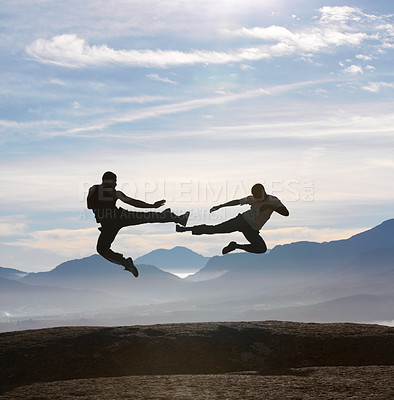 Buy stock photo Two male kickboxers fly kicking one another on a mountain top