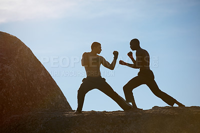 Buy stock photo Two friends practicing their kickboxing on a mountain top