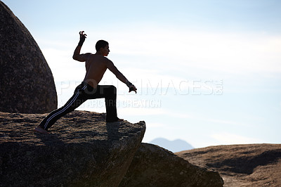 Buy stock photo A male kickboxer practising on the edge of a cliff on a mountain