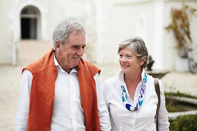 Buy stock photo A happy senior couple talking a walk together while on vacation