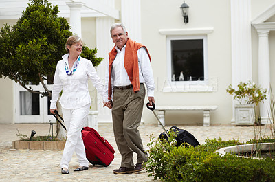 Buy stock photo Portrait of a senior couple arriving at their hotel with their suitcases in tow