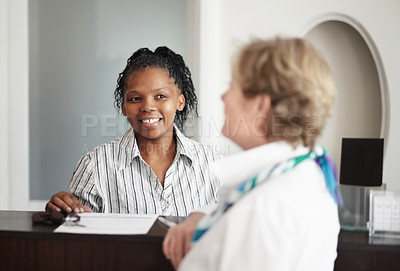 Buy stock photo A receptionist giving a senior woman the keys to her hotel room