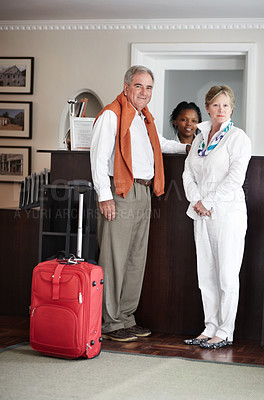 Buy stock photo A senior couple checking in at the reception desk of their hotel