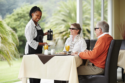 Buy stock photo A senior couple being served a scrumptious breakfast while on holiday
