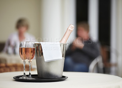 Buy stock photo A champagne bottle and two champagne glasses on a restaurant table