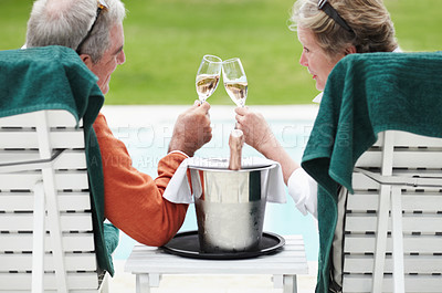 Buy stock photo Rear view of a senior couple clinking their champagne glasses together while on vacation