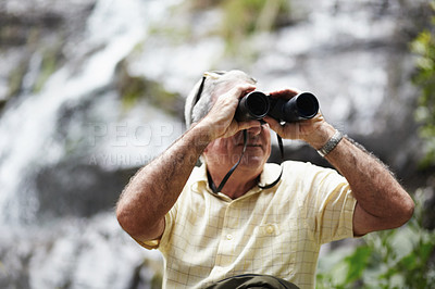 Buy stock photo Shot of a senior man looking at scenery with a pair of binoculars
