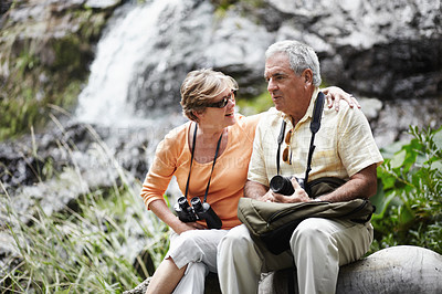 Buy stock photo A senior couple taking a break while out walking in the forest together