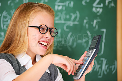 Buy stock photo A cute blonde girl adding on her calculator in class