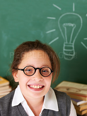 Buy stock photo Portrait of a cute brunette girl in class with a chalk lightbulb on the board in the background