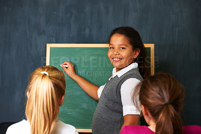 Buy stock photo Portrait of a cute girl showing her two friends something on the chalkboard in class