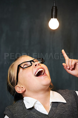 Buy stock photo A cute blonde girl pointing up at a light bulb in class