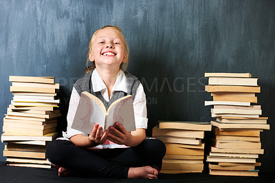 Buy stock photo A cute blonde girl studying in class surrounded by books