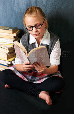 Buy stock photo A cute blonde girl reading peacefully in class surrounded by books
