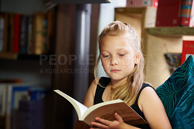 Buy stock photo A cute blonde girl reading intently on the couch