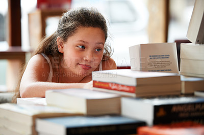 Buy stock photo A cute brunette girl looking at a pile of books in the library