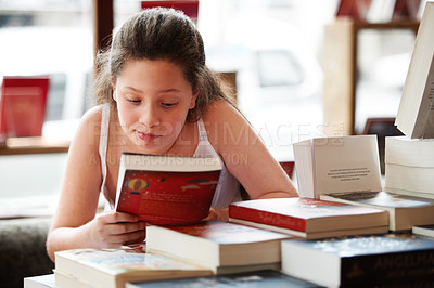 Buy stock photo A cute brunette girl looking at the cover of a book in the library