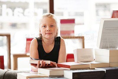 Buy stock photo Portrait of a cute blonde girl holding a book in the library