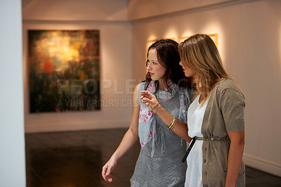 Buy stock photo Two young woman examining a painting up close while attending an exhibition