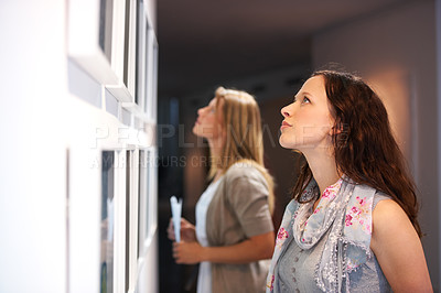 Buy stock photo Two female friends closely scrutinizing a painting at an exhibition