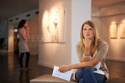 Buy stock photo Two young friends looking at paintings while attending an exhibition