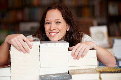 Buy stock photo Portrait of a young woman leaning over stacks of books