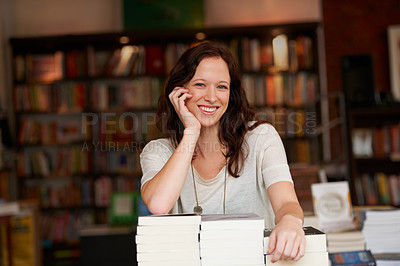 Buy stock photo Portrait of a young woman leaning on stacks of books in a bookstore