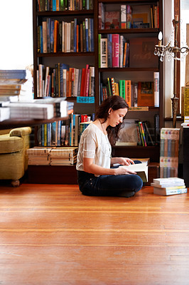 Buy stock photo A young woman sitting on the floor with her legs crossed and reading