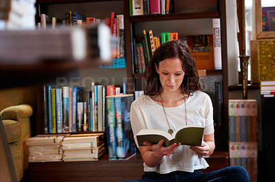 Buy stock photo A young woman sitting on the floor of a bookstore reading