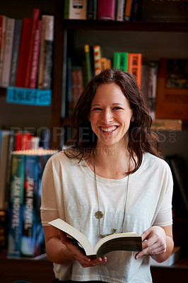 Buy stock photo Portrait of a smiling young woman reading a book against a backdrop of bookshelves