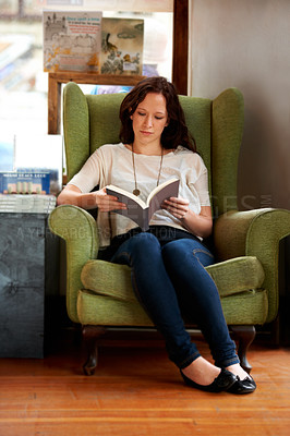 Buy stock photo A young woman sitting in a comfy chair and reading
