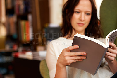 Buy stock photo A young woman quietly reading a book while seated in a chair