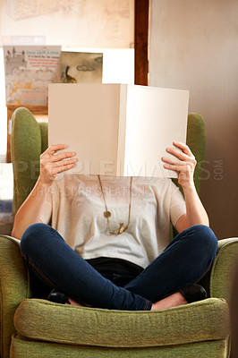 Buy stock photo A young woman sitting in a chair with a book held up close to her face