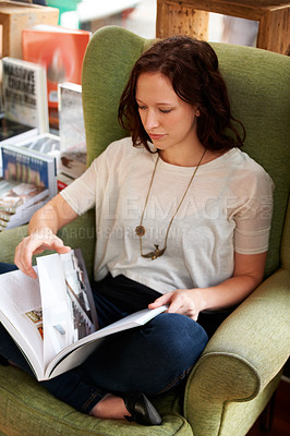 Buy stock photo A high angle shot of a young woman sitting in a chair and reading