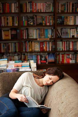 Buy stock photo A young woman relaxing on a sofa with a good book
