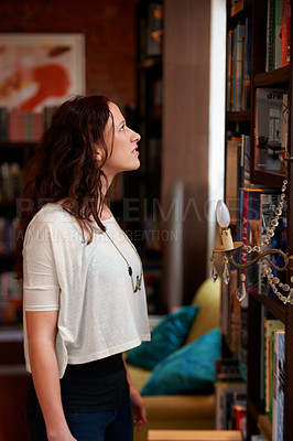 Buy stock photo A young woman browsing the bookshelves of a bookstore