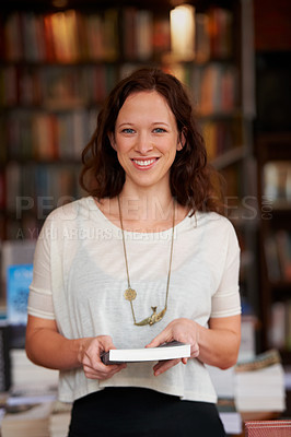 Buy stock photo Portrait of a smiling woman holding a book against a backdrop of bookshelves