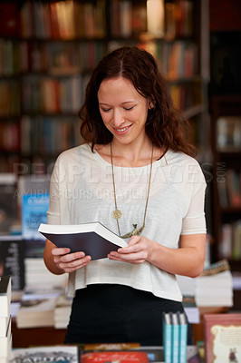 Buy stock photo A young woman reading the back cover of a novel while browsing in a bookshop