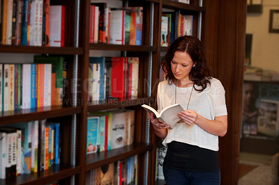 Buy stock photo A young woman leans against some shelves while leafing through the pages of a book