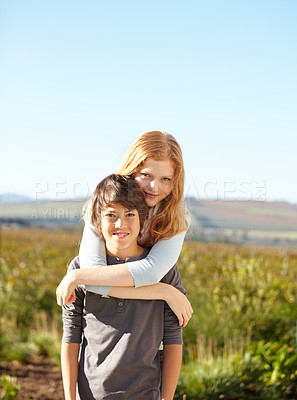 Buy stock photo Portrait of a young boy giving his sister a piggyback in the garden