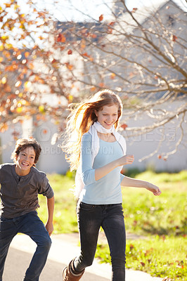 Buy stock photo A brother and sister playfully running together in the street