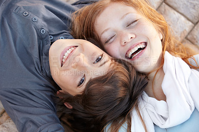 Buy stock photo Portrait of a brother and sister lying on the floor with their heads together